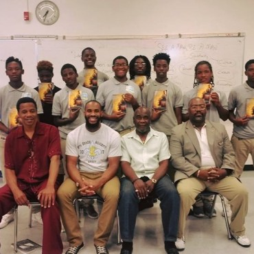 "Mentors sitting as the future leaders hold up their personal copies of ""The Black Male Handbook: A Blueprint for Life"" by Kevin Powell"